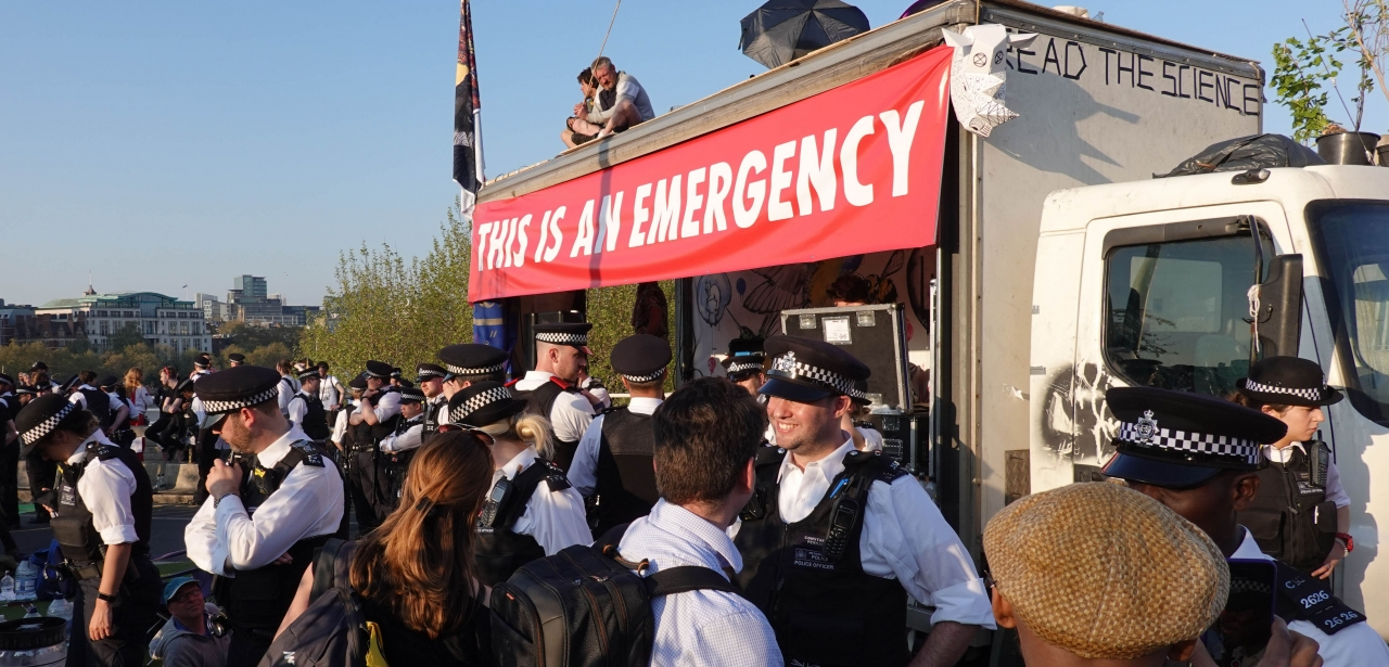 Extinction Rebellion activists and police surround a vehicle during a protest on Waterloo Bridge