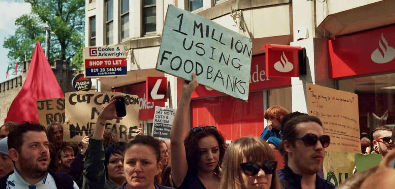 At an anti-austerity protest a placard reads '1 million using food banks'