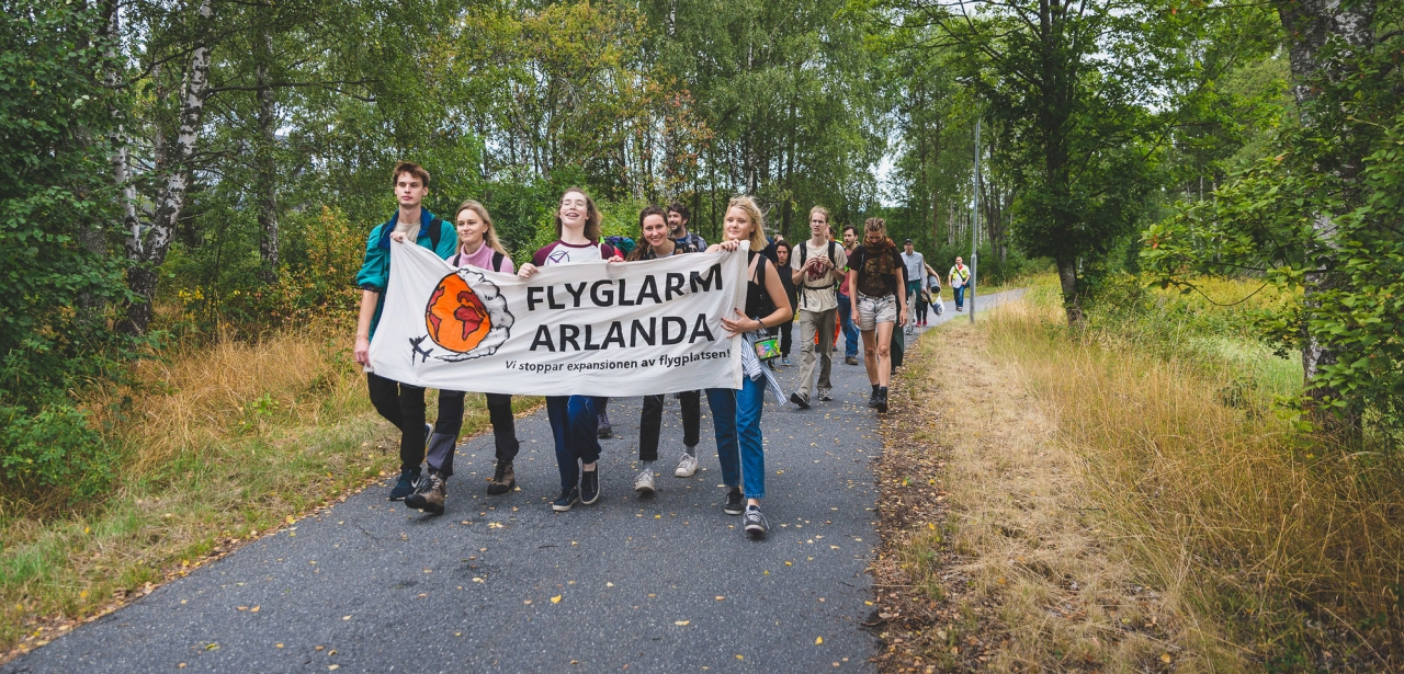 Protesters from Flyglarm Arlanda group walking with banner