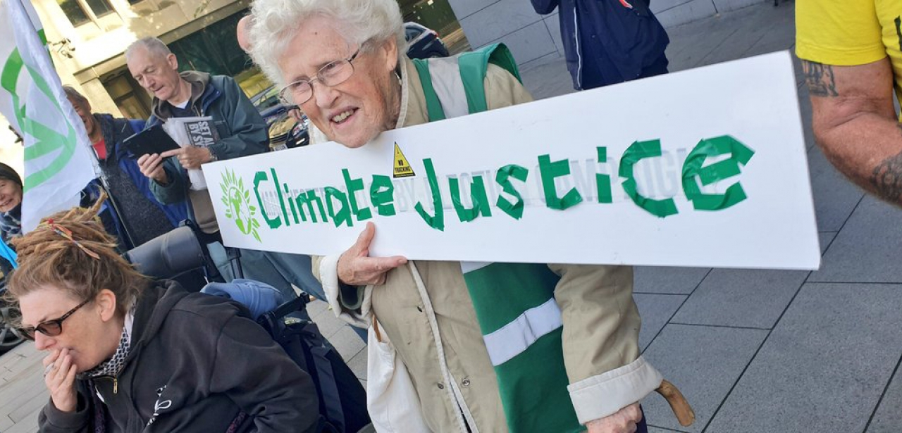 Extinction Rebellion protester with placard reading 'Climate Justice'