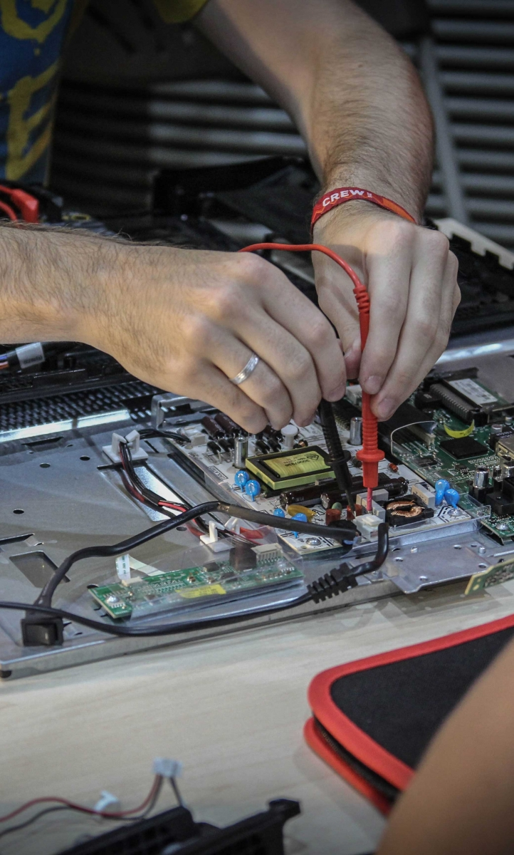 Image of someone's hands as they fix electronics in a laptop