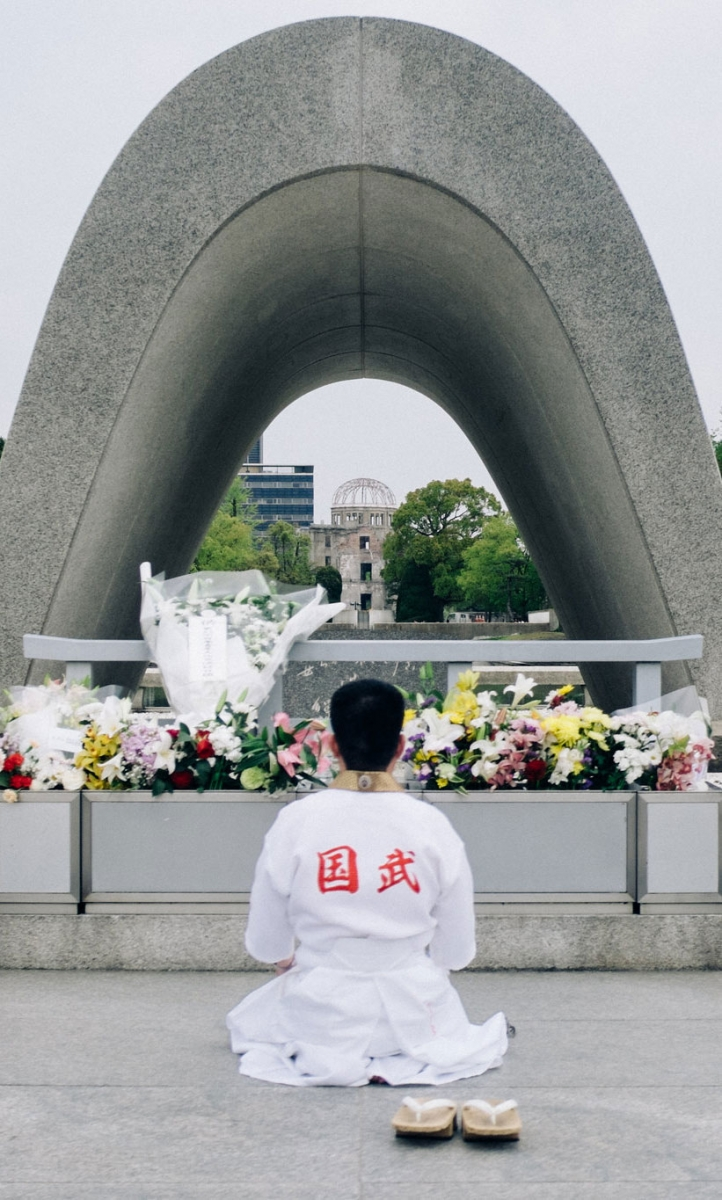 A man kneeling in front of the Hiroshima Memorial Cenotaph with flowers