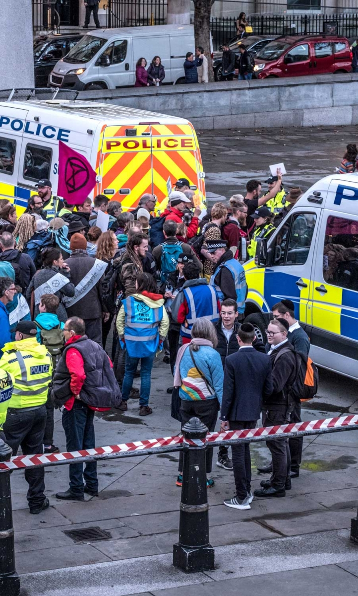 Police officers controlling a group of Extinction Rebellion protestors