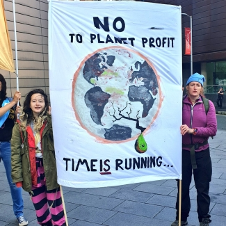 Two protesters with a large banners: 'No to planet profit'