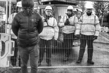A protester stands in front of a fence and Amey workers