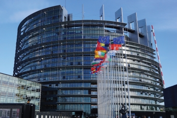 A image of the European Parliament building with flags of EU states