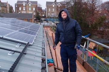 Ian Mecklenburgh of Alian Energy installing a rooftop solar thermal system
