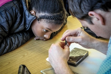 A young girl watches a man fix a mobile phone screen