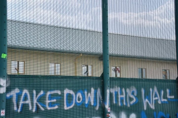 Hands wave out of windows behind a high fence at Yarl's Wood detention centre