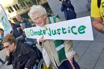Protester holding placard that says 'Climate Justice'