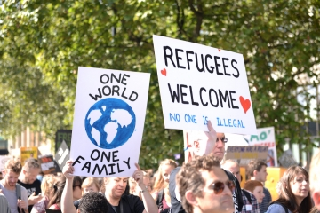 Signs saying 'Refugees welcome' at a protest.
